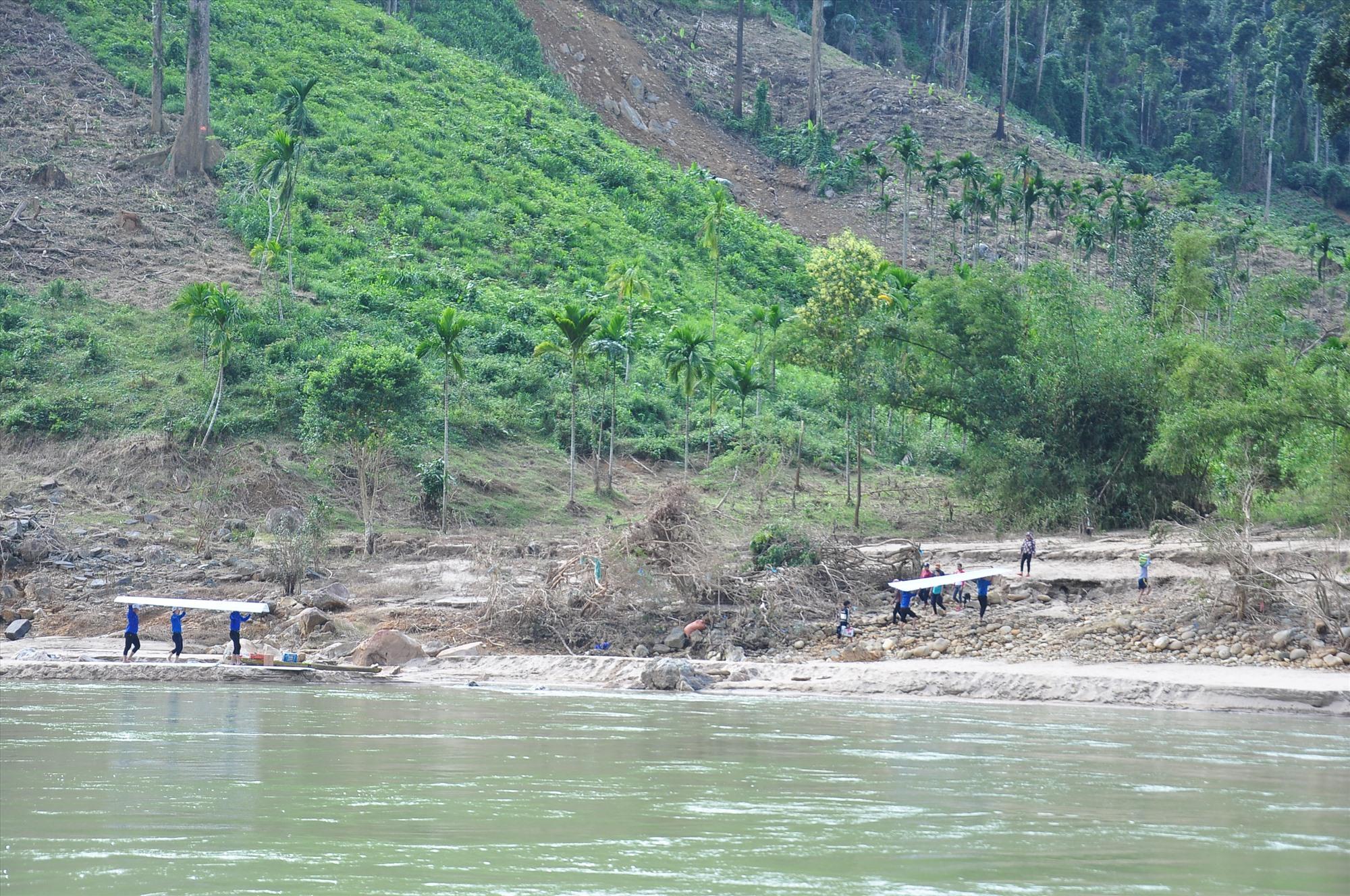 Sau vượt sông, thanh niên tình nguyện tiếp tục cõng tôn đi vào làng Tắk Rối. Ảnh: VINH ANH