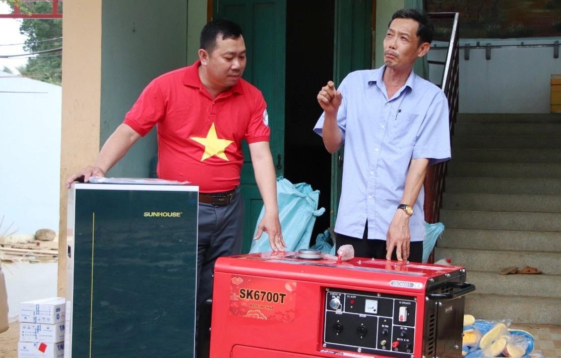 Thầy Bùi Quang Ngọc, Hiệu trưởng Trường Phổ thông dân tộc bán trú tiểu học Trà Leng (phải) vui mừng tiếp nhận máy phát điện, máy lọc nước.