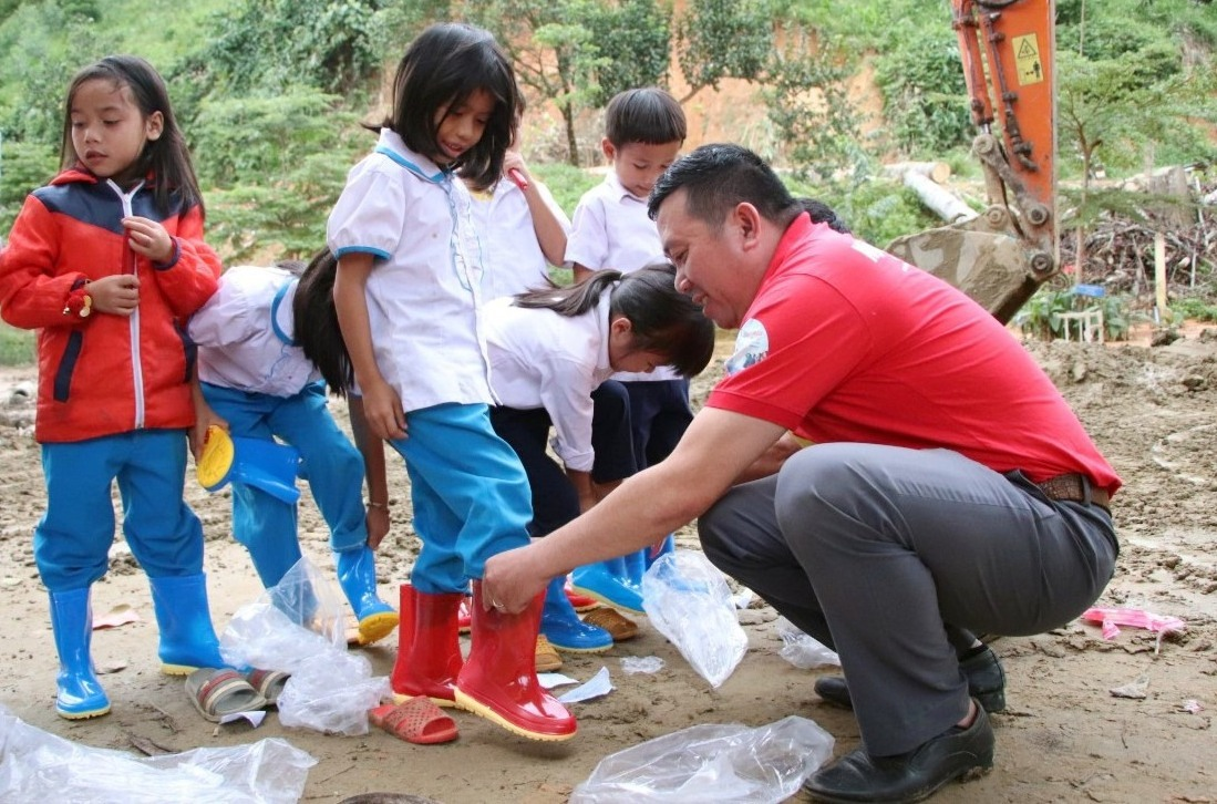 Đại diện Báo Người Lao Động tặng ủng cho các em học sinh Trà Leng.