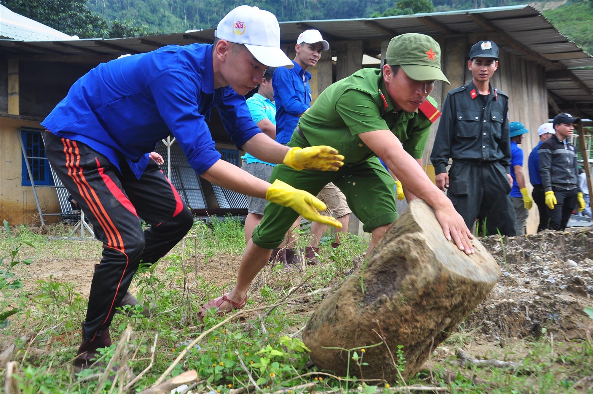 Lực lượng tình nguyện làm việc hăng say giúp nhà trường khắc phục hậu quả bão lũ. Ảnh: VINH ANH