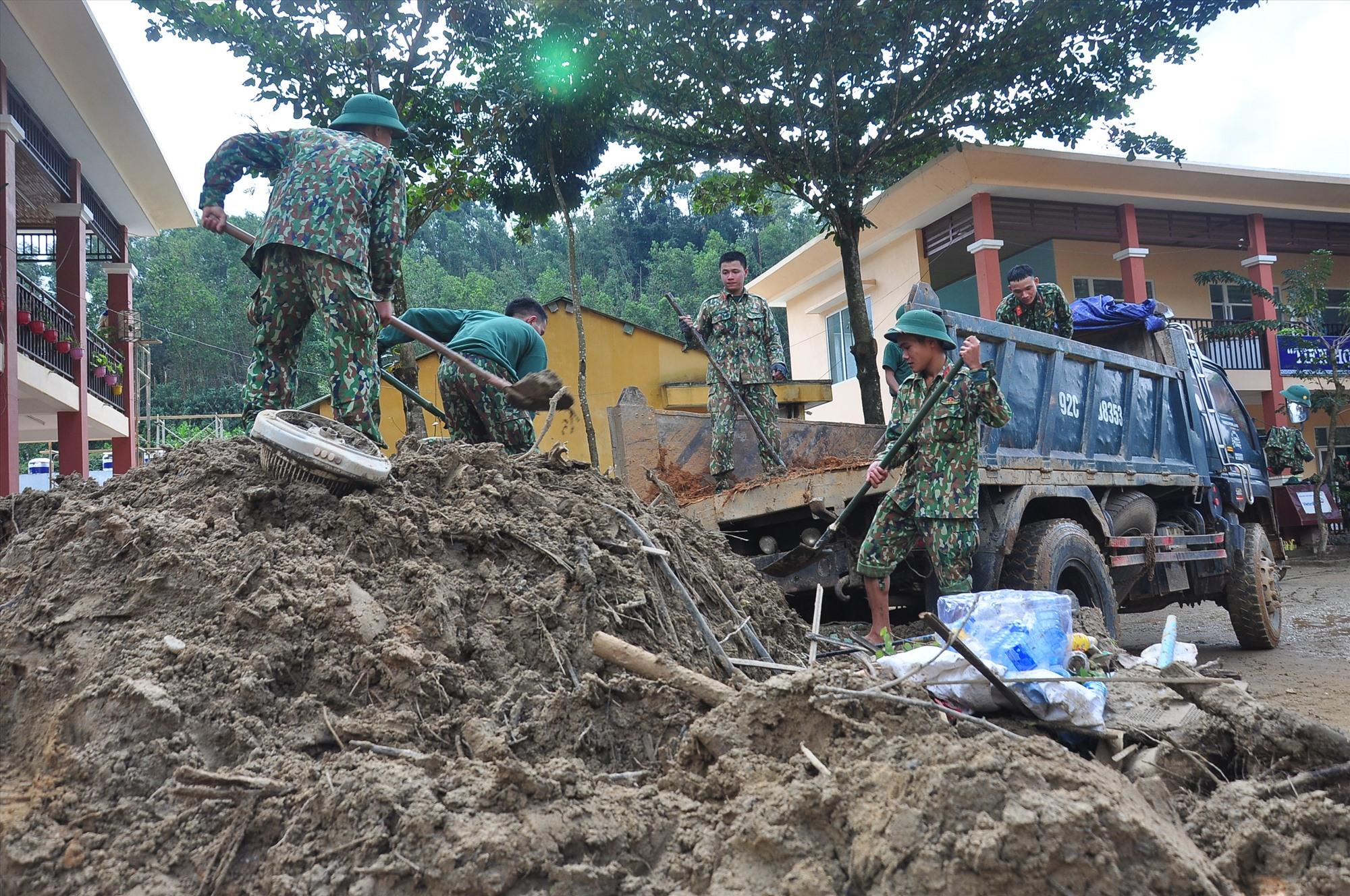 Sử dụng xe tải để vận chuyển bùn đất trong sân trường ra ngoài. Ảnh: VINH ANH
