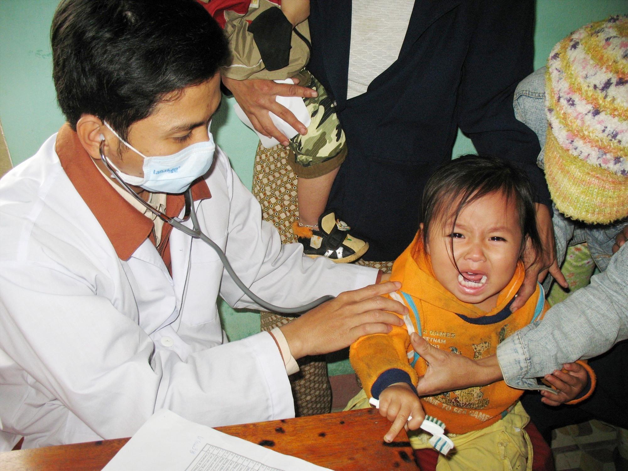 Người dân đưa trẻ đi tiêm vắc xin tại một TYT xã. Ảnh: X.H