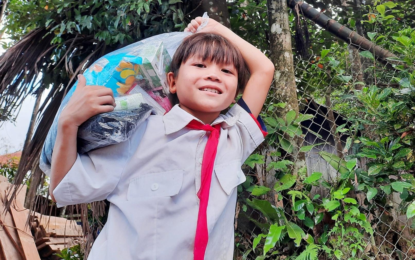 Một cậu học sinh làng Tăk Pát vui mừng vì được áo quần, bánh kẹo do địa phương hỗ trợ. Ảnh: HỒ QUÂN