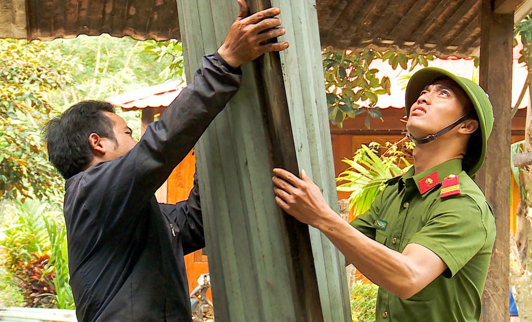 Cán bộ công an và người dân cùng nhau dựng nhà, vượt qua khó khăn. Ảnh: HỒ QUÂN