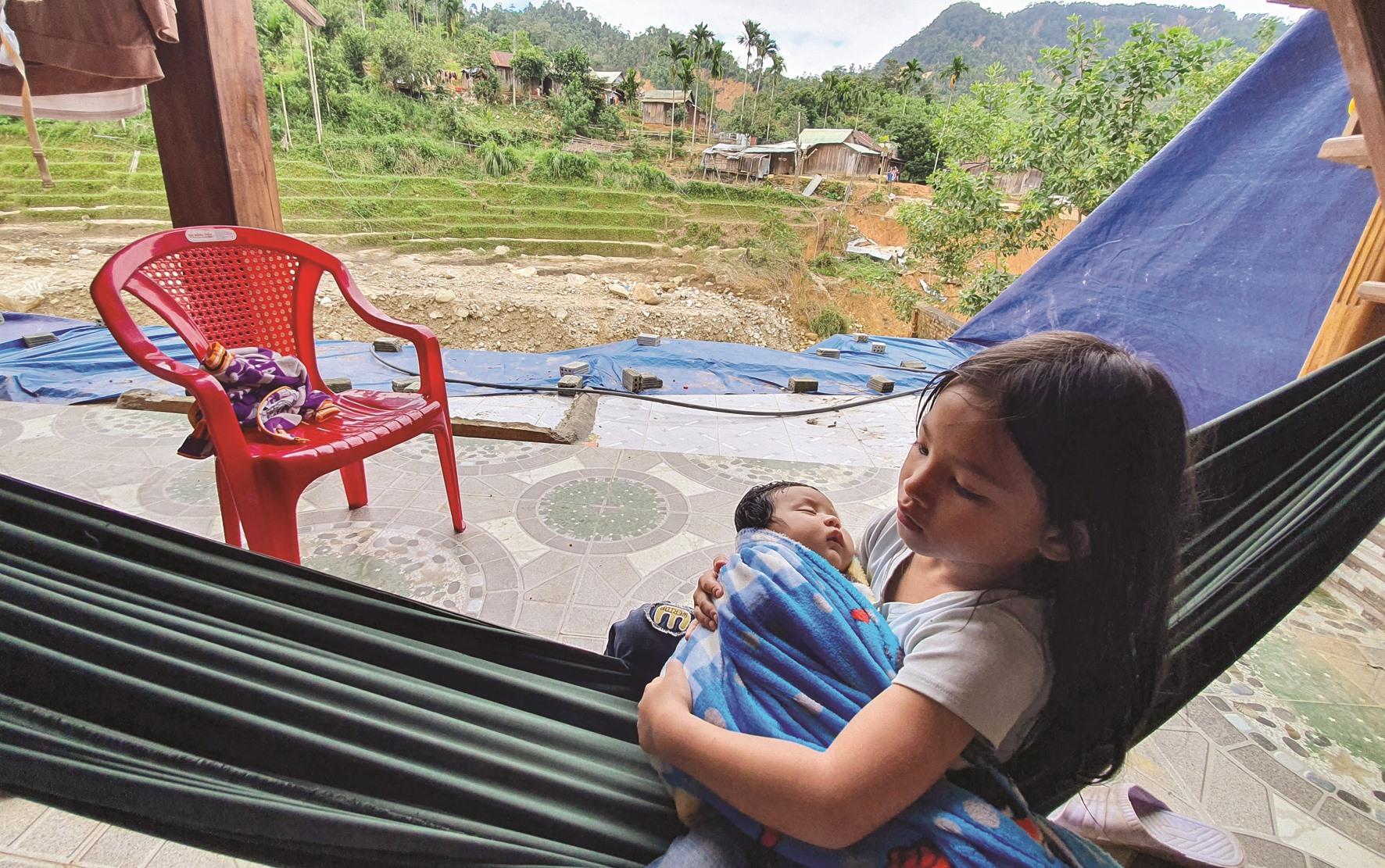 Hai đứa con của chị Hồ Thị Hoa bên căn nhà trống hoác vì sạt lở. Ảnh: T.C