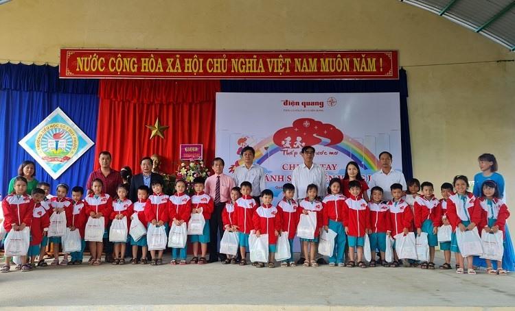 Lãnh đạo công ty Điện Quang tặng quà cho học sinh trường Tiểu học Duy Phước.