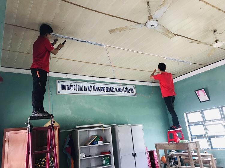 Cán bộ kỹ thuật Công ty Điện Quang hỗ trợ lắp đặp hệ thống đèn chiếu sáng tại trường tiểu học Duy Phước.