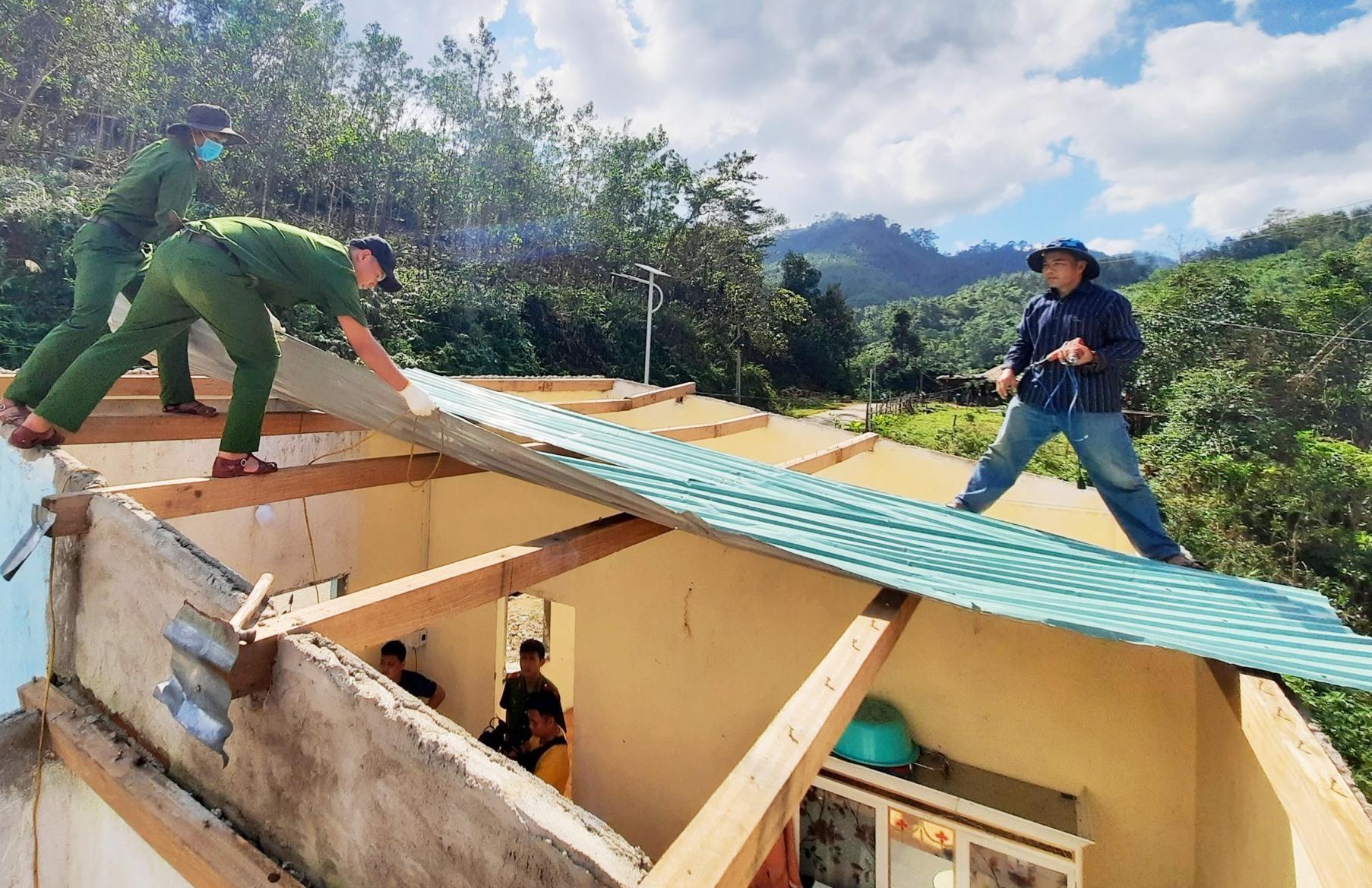 Ra quân tháo dỡ phần mái nhà cũ của một người dân ở Bắc Trà My bị bão thổi bay và lợp lại mái mới. Ảnh: HỒ QUÂN