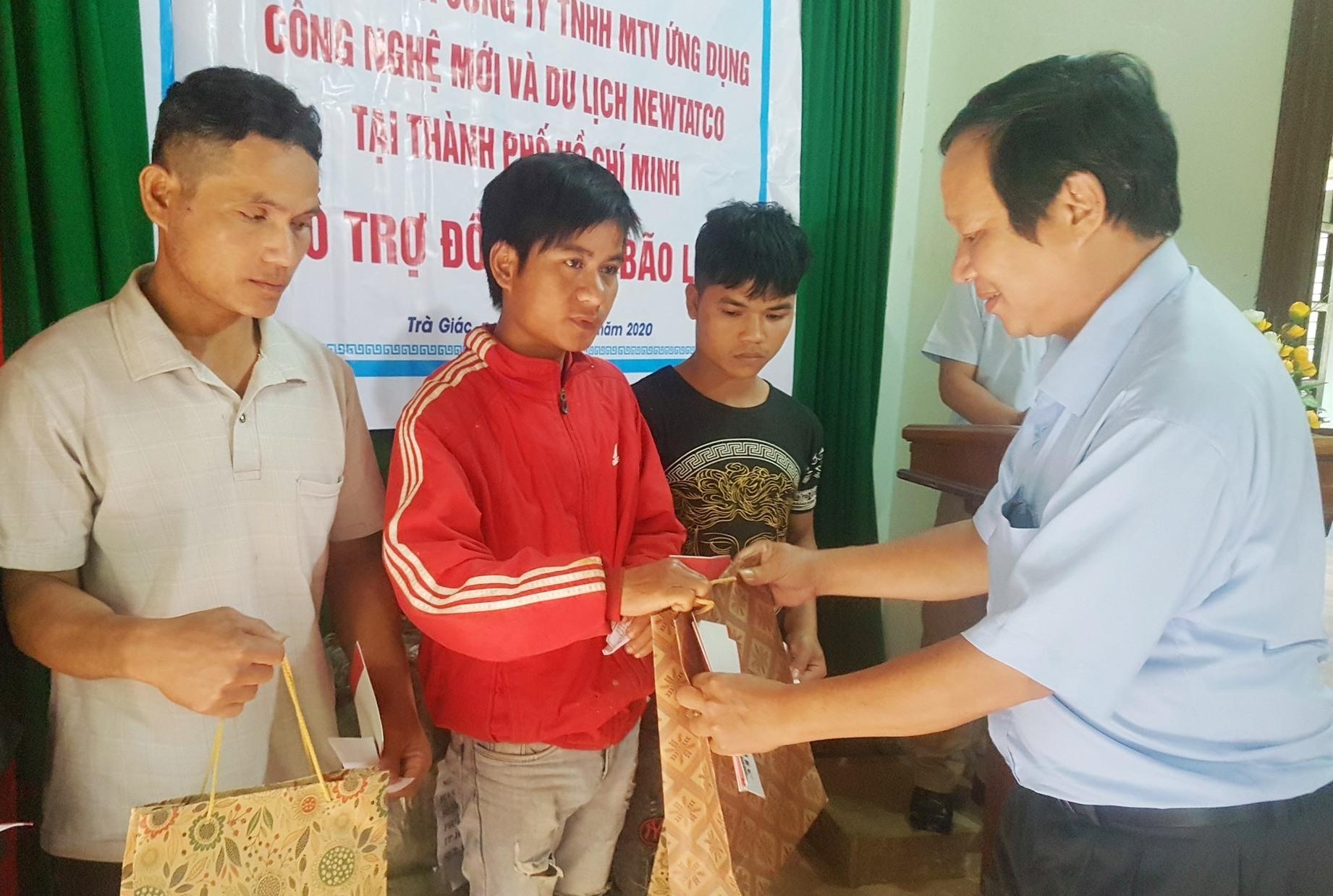 Lãnh đạo Trung tâm Dịch vụ việc làm tỉnh trao quà hỗ trợ người dân xã Trà Giác. Ảnh: D.L