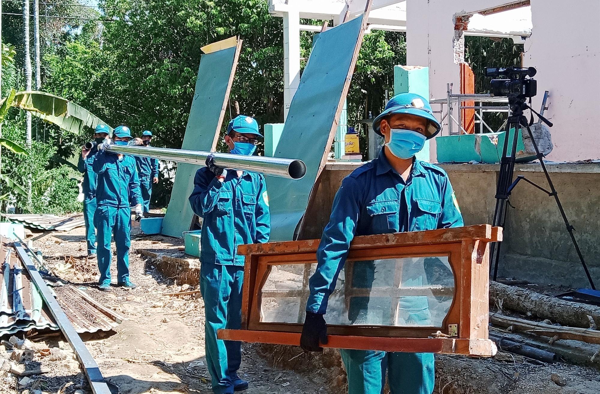 Lực lượng dân quân thị trấn Tân Bình giúp dân di dời nhà cửa.