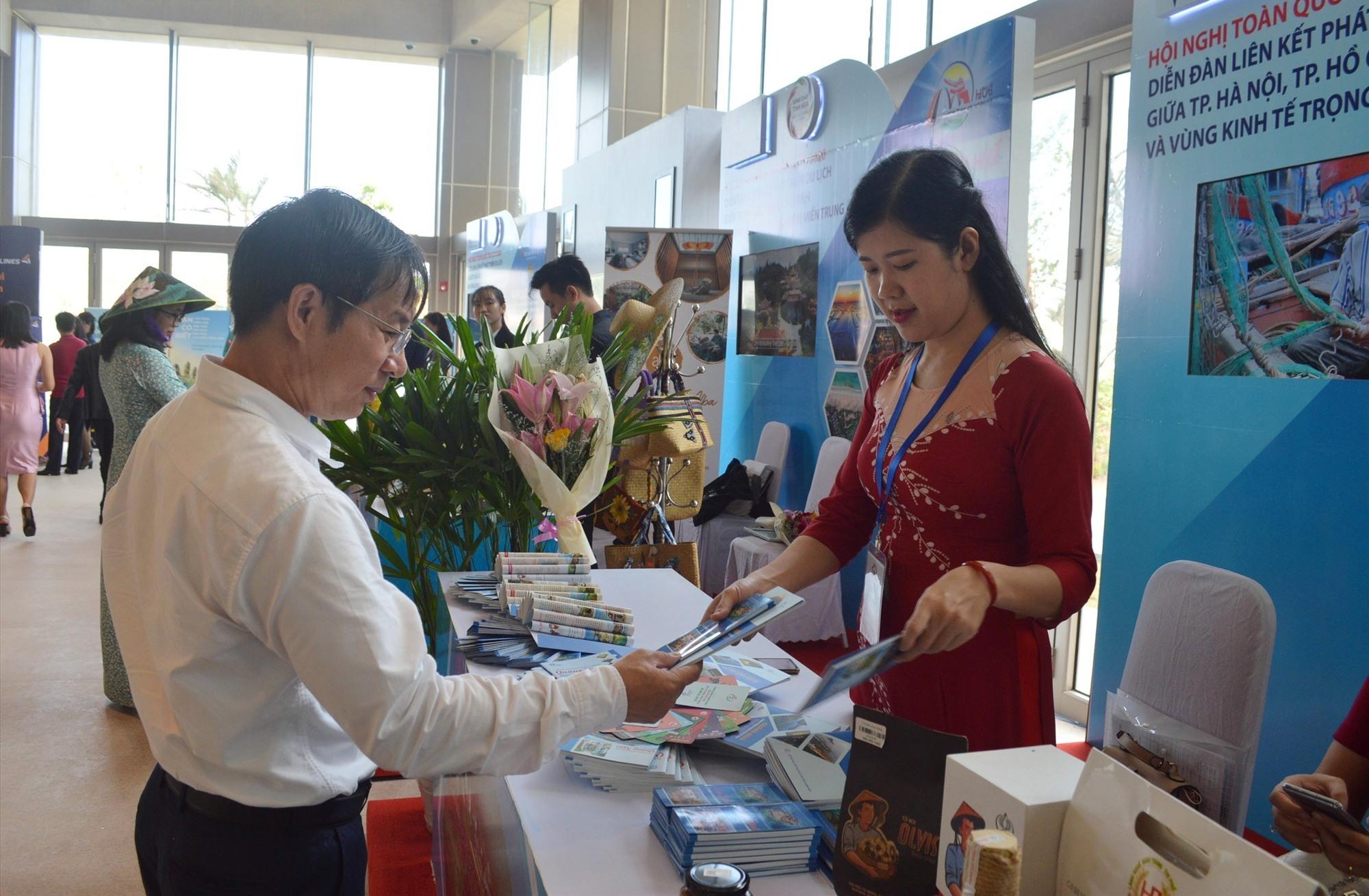 Đại biểu tìm hiểu các gian hàng du lịch các địa phương trưng bày bên lề sự kiện Diễn đàn du lịch