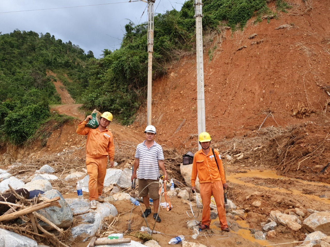 CBCNV Điện lực Hiệp Đức nỗ lực khắc phục hậu quả bão lũ, hoàn thành cấp điện lại phục vụ người dân xã Phước Lộc. Ảnh: KIÊN PHAN