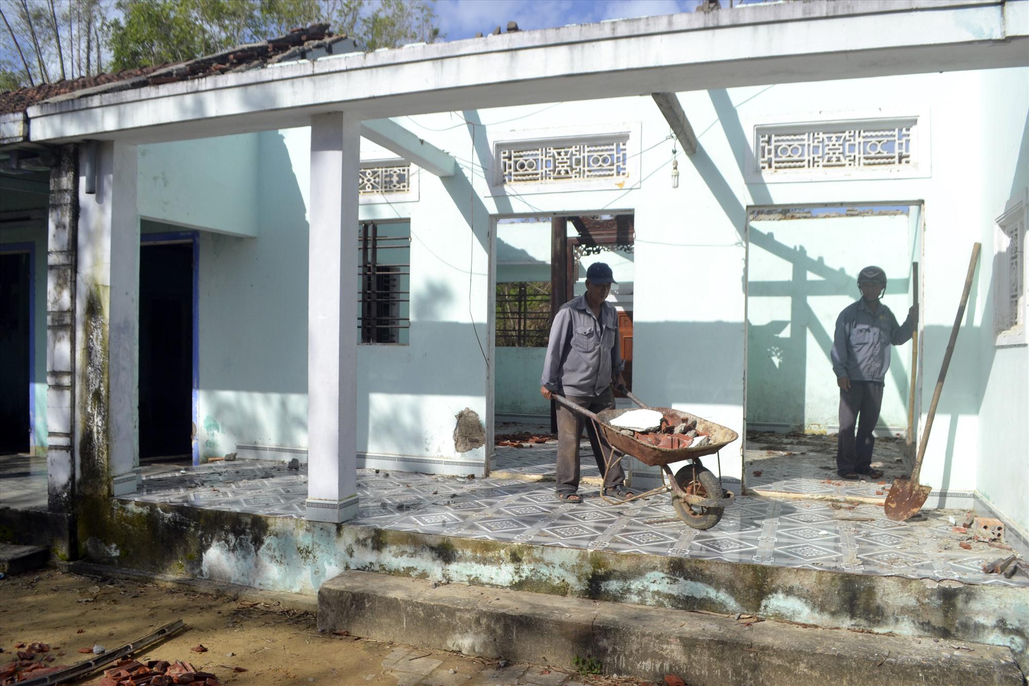 Nhà thầu hỗ trợ nhân lực để tháo dỡ nhà cửa cho hộ bà Nguyễn Thị Vân. Ảnh: C.T