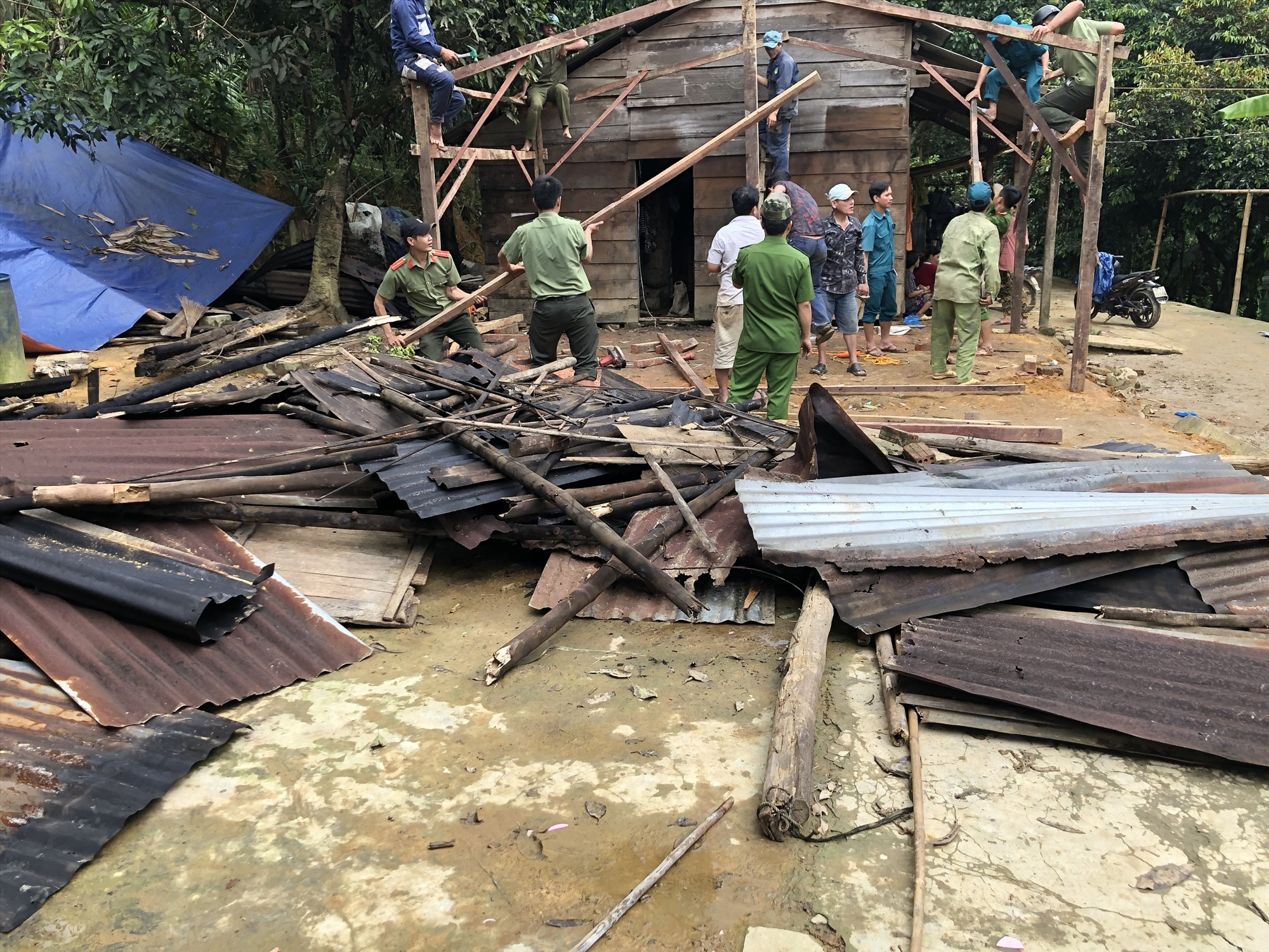 Cán bộ, chiến sĩ Công an cùng người dân dựng lại nhà cho một hộ dân ở xã Phước Đức (Phước Sơn). Ảnh: M.T