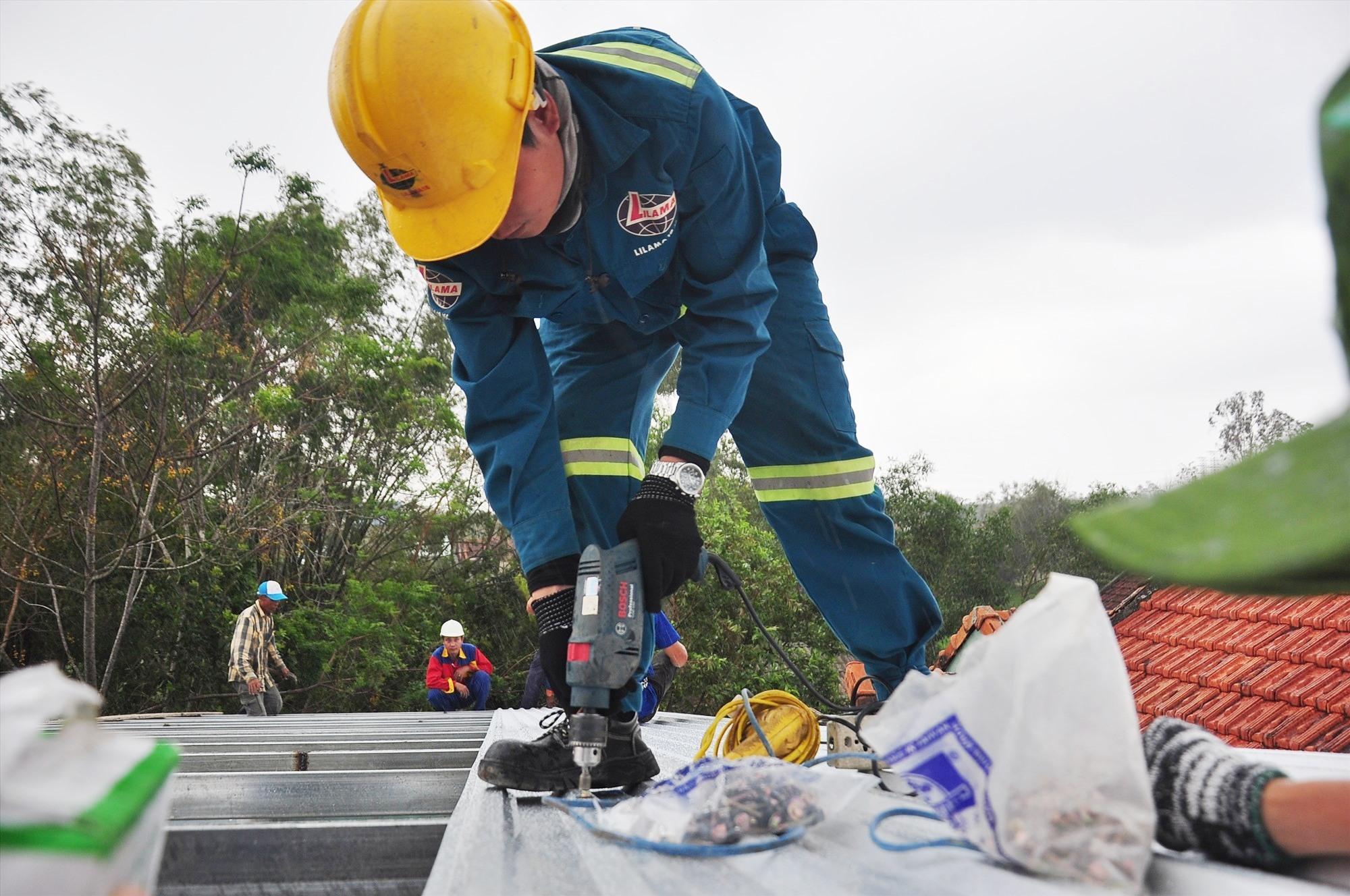 Thanh niên Công ty CP Lilama 18 tham gia cùng đoàn tình nguyện sửa nhà giúp dân. Ảnh: V.A