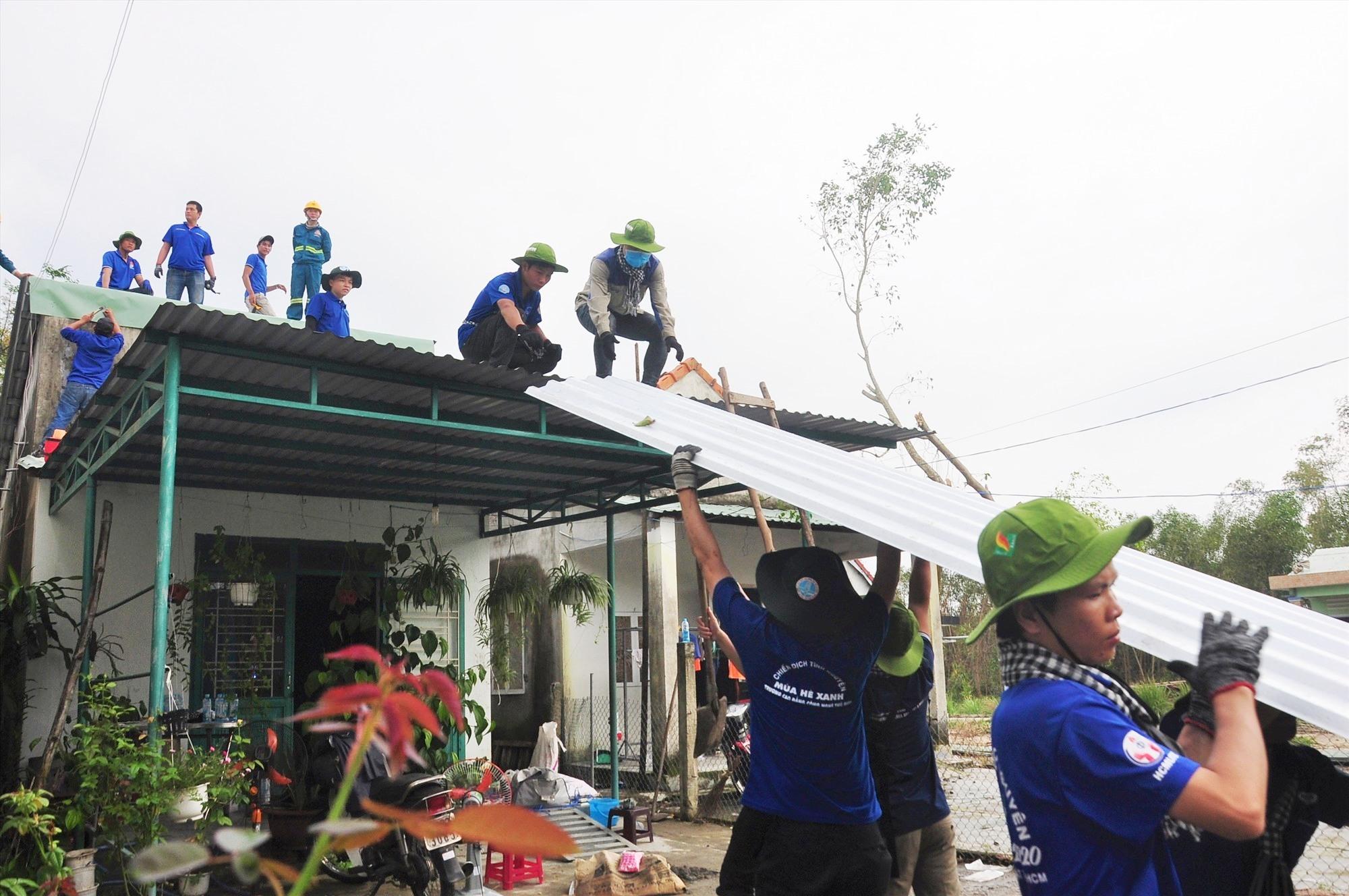 Vận chuyển tôn lên mái nhà lợp cho người dân. Ảnh: V.A