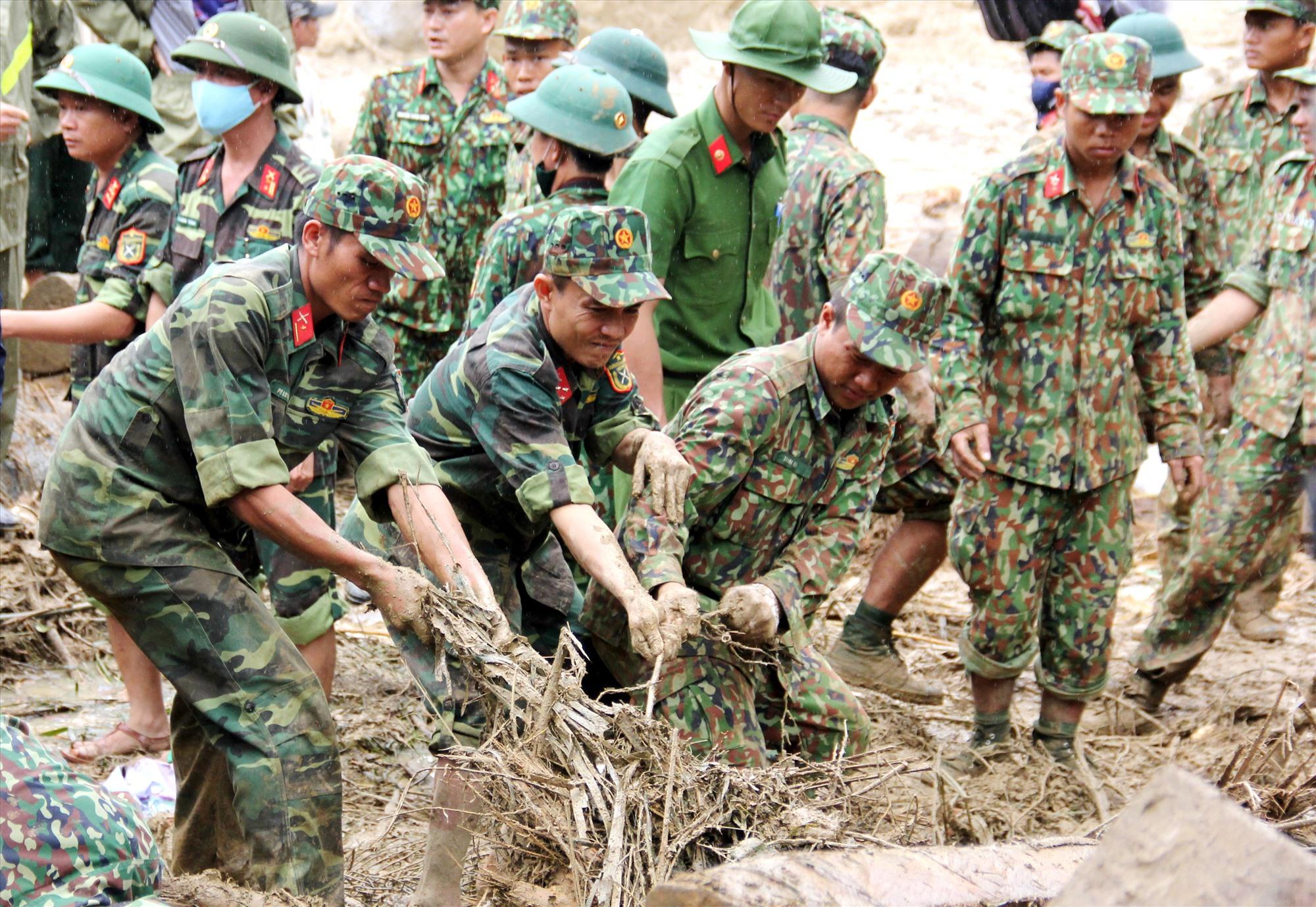 Các chiến sĩ dầm mưa tìm kiếm nạn nhân mất tích ở xã Trà Leng (Nam Trà My). Ảnh: NGƯỚC ANH