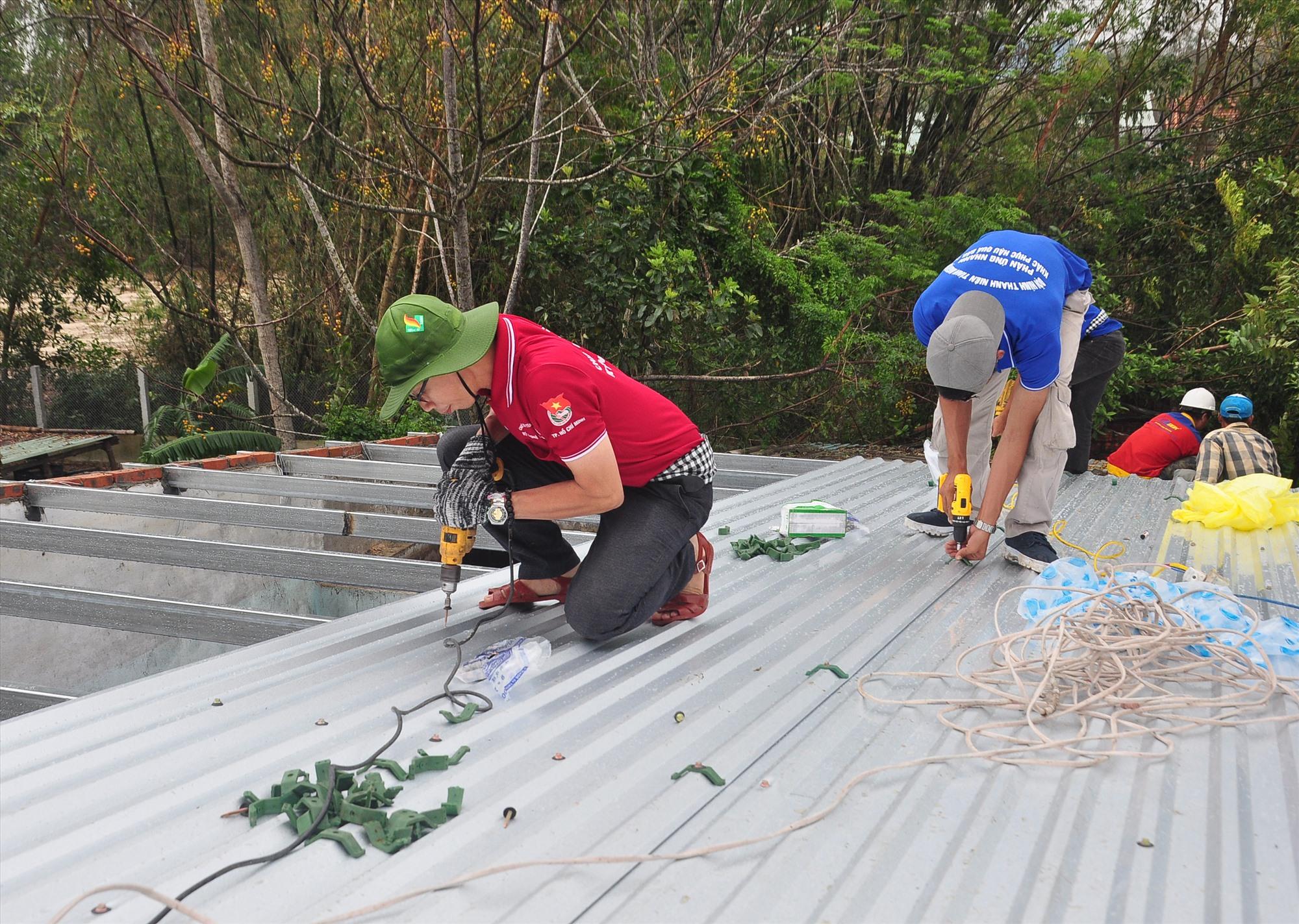 Thanh niên tình nguyện sửa chữa nhà cho người dân. Ảnh: ANH NGƯỚC