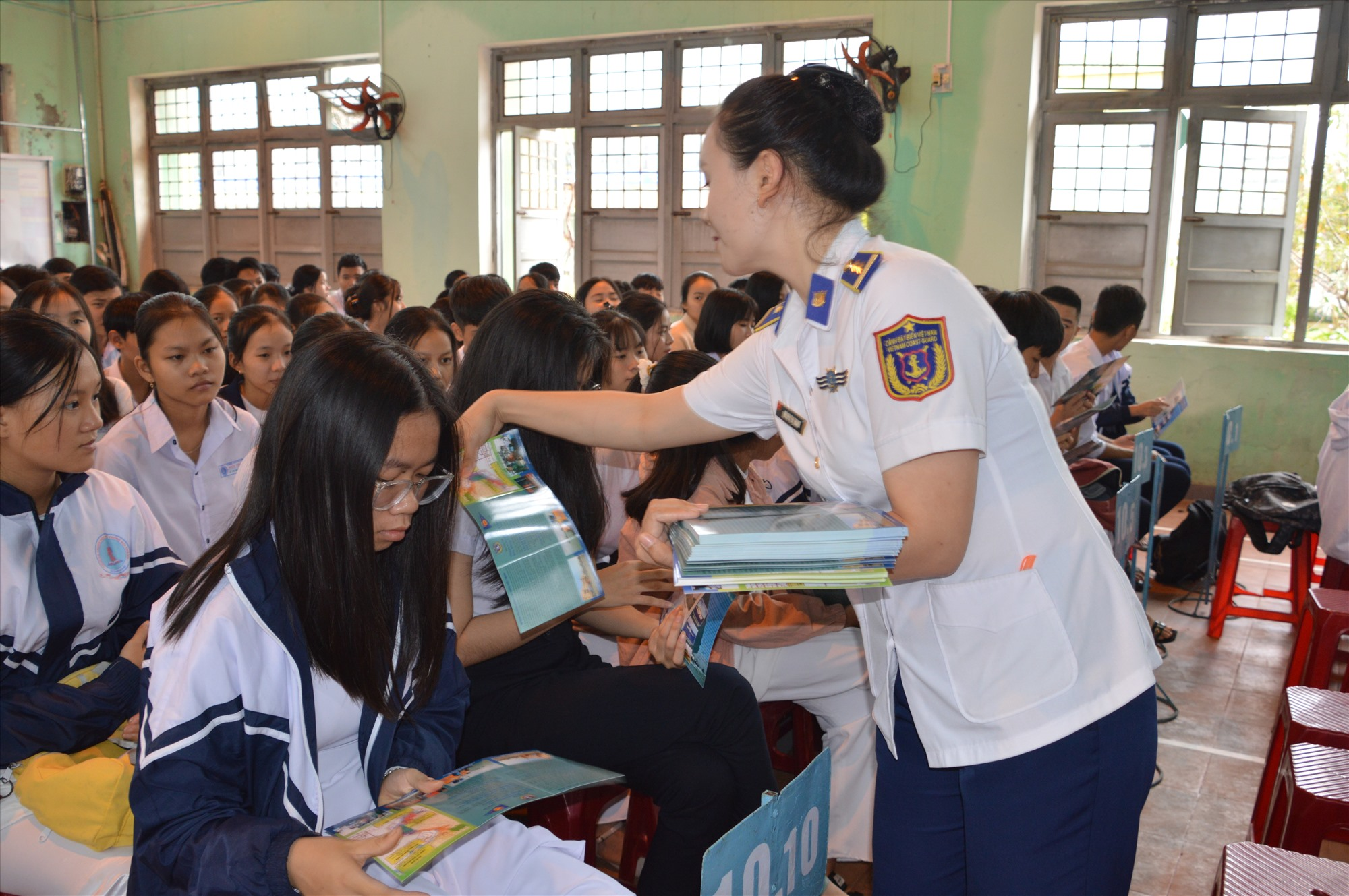 Phát tờ rơi tuyên truyền cho các em học sinh tại lễ phát động cuộc thi. Ảnh: N.T