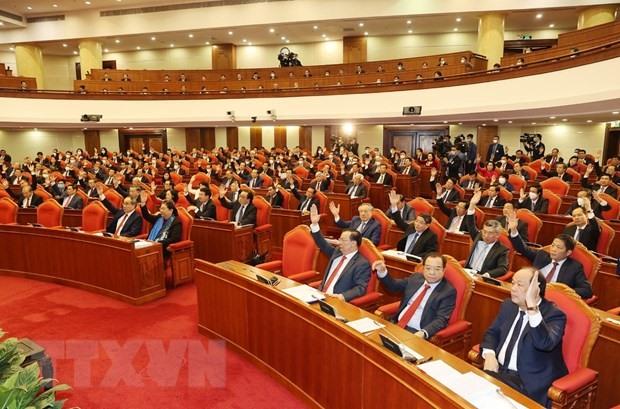 Các đồng chí lãnh đạo Đảng, Nhà nước và các đại biểu biểu quyết thông qua chương trình Hội nghị. (Ảnh: Trí Dũng/TTXVN)