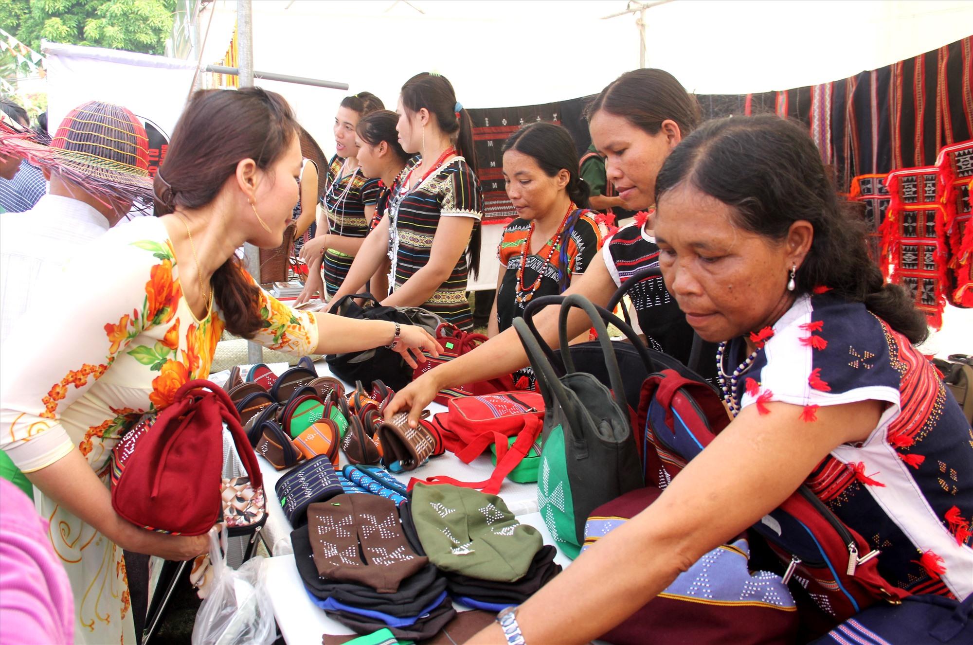 Các hội viên Hợp tác xã Dệt thổ cẩm Cơ Tu Za Ra giới thiệu sản phẩm túi Ađhir cho khách tại hội chợ triển lãm. Ảnh: ĐĂNG NGUYÊN