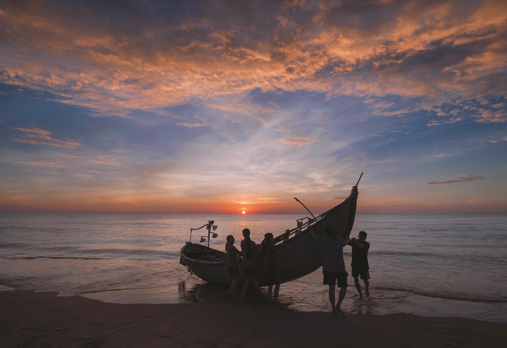 Một chiếc thuyền vào bờ lúc mặt trời vừa mọc.