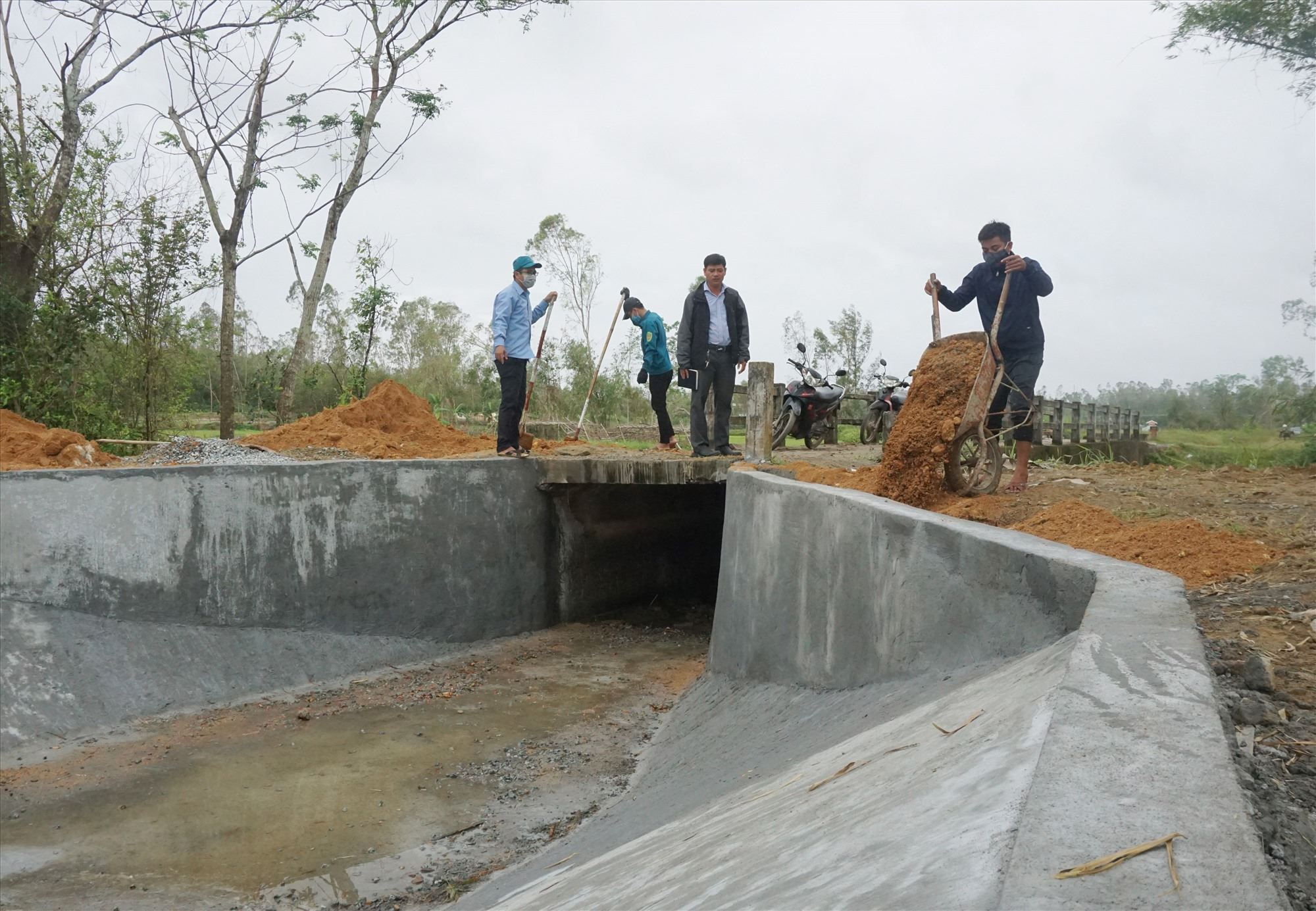 Chi nhánh Thủy lợi huyện Thăng Bình huy động lực lượng để khắc phục các điểm sạt lở kênh mương do mưa bão vừa qua. Ảnh: G.B