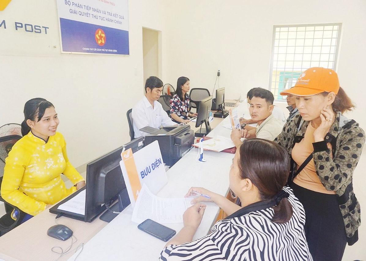 Người dân đến làm thủ tục hành chính tại Bưu điện xã Bình Triều, huyện Thăng Bình. Ảnh: B.Đ