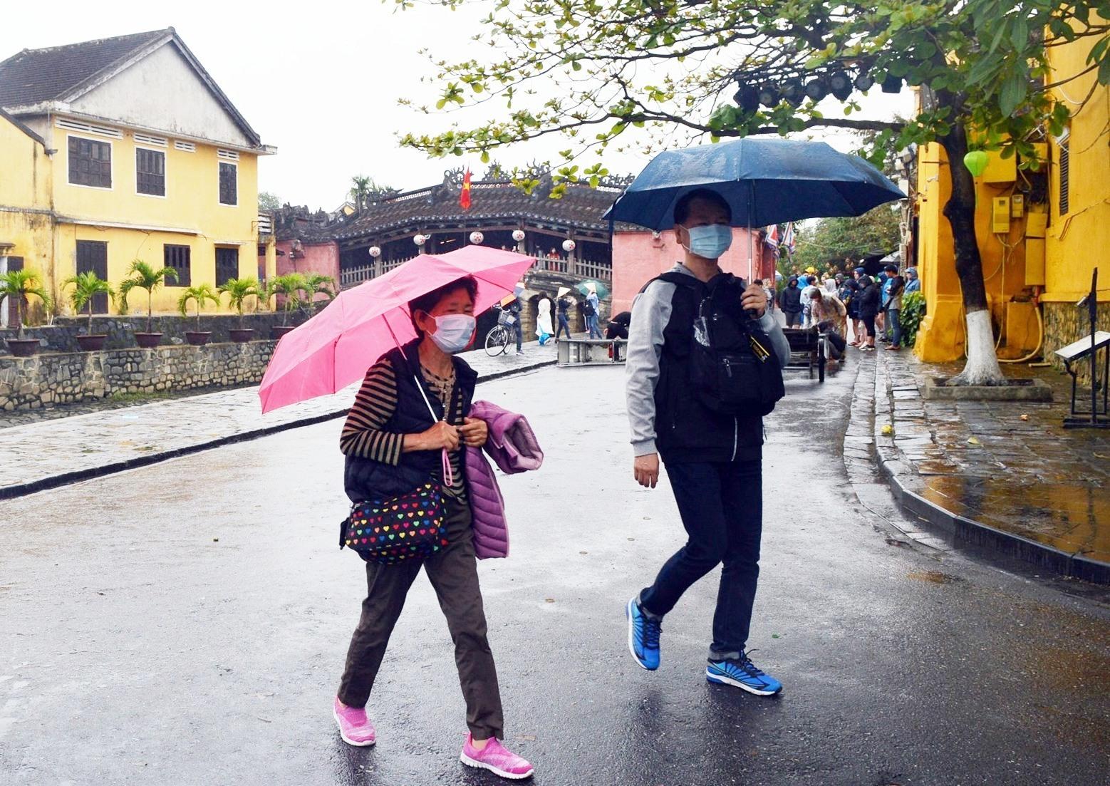 Du khách đeo khẩu trang tham quan phố cổ Hội An
