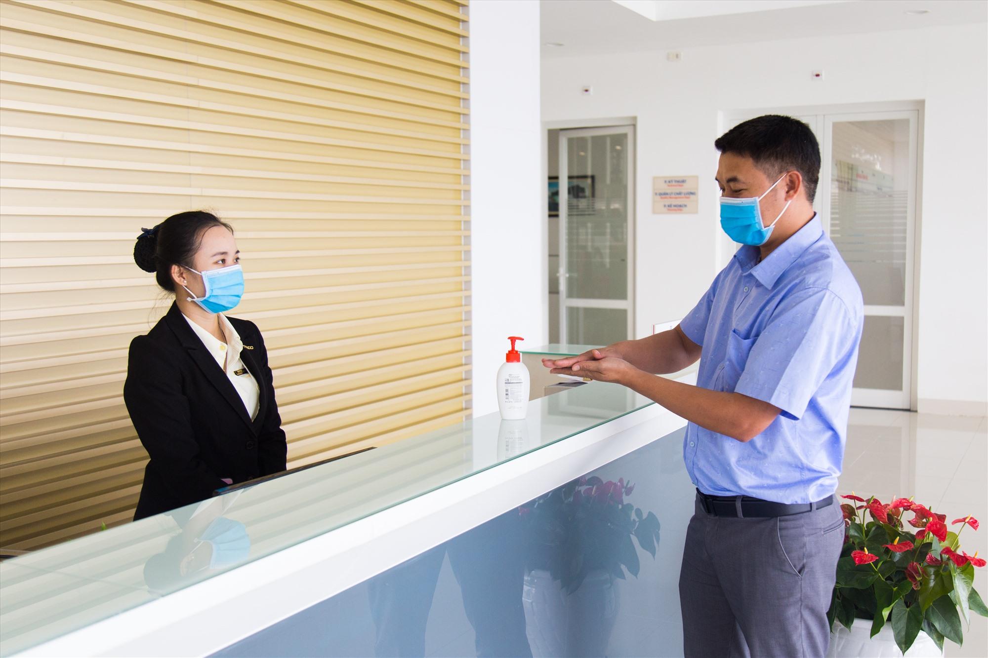 Nhân viên Lễ tân NM THACO Bus hướng dẫn khách rửa tay bằng cồn sát khuẩn khi làm việc tại nhà máy
