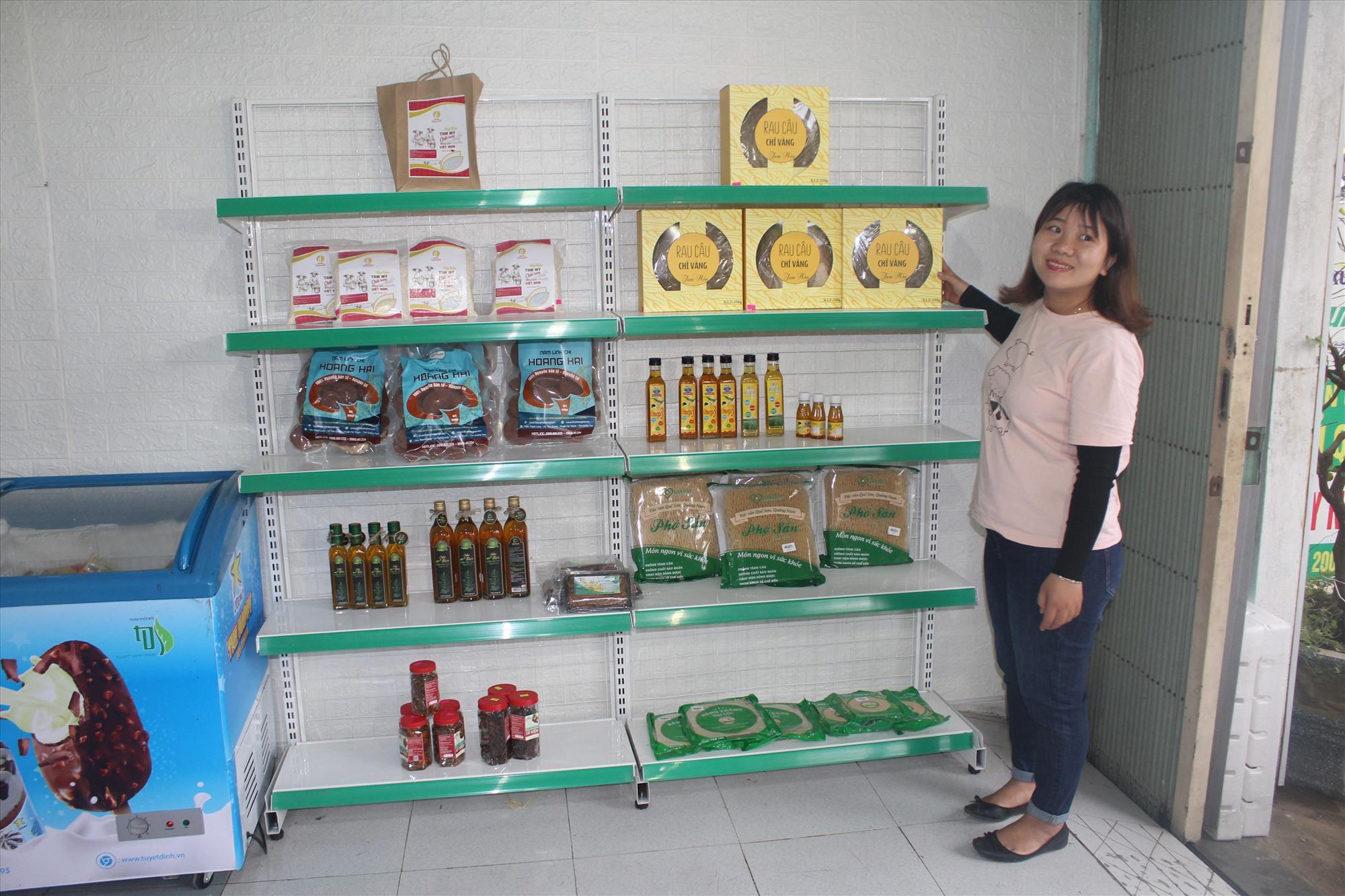 Chị Sang và các sản phẩm OCOP trưng bày tại cửa hàng. Ảnh: VĂN PHIN