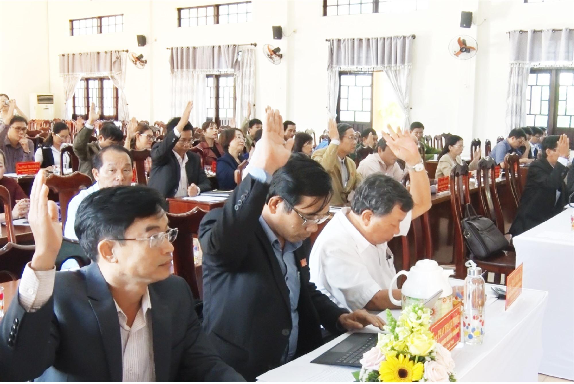 Các đại biểu HĐND huyện biểu quyết thông qua Nghị quyết miễn nhiệm các chức danh do HĐND huyện bầu.