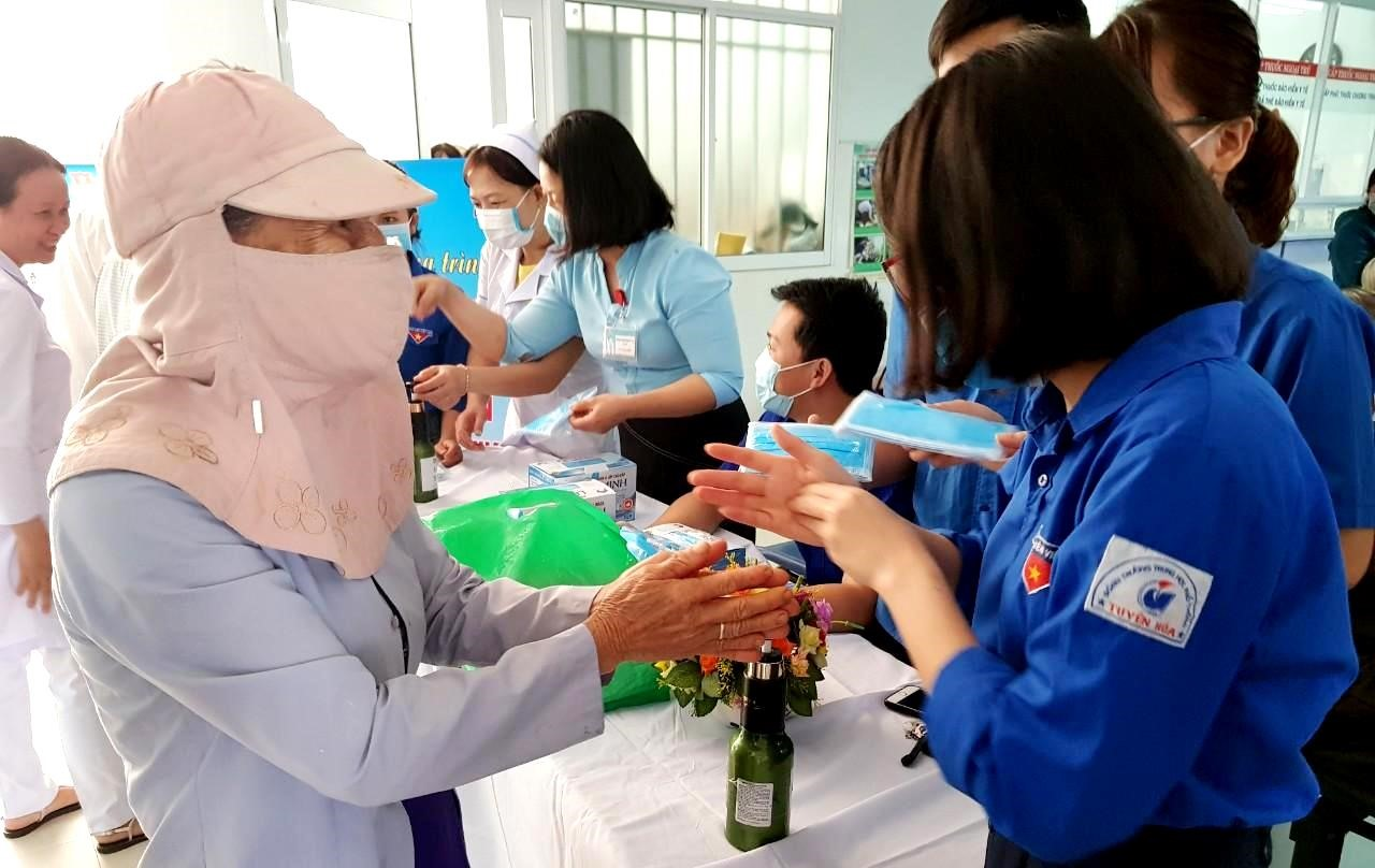 Người dân được đoàn viên Đoàn thanh niên Bệnh viện Đa khoa tỉnh hướng dẫn vệ sinh bằng dung dịch diệt khuẩn. Ảnh: CTV