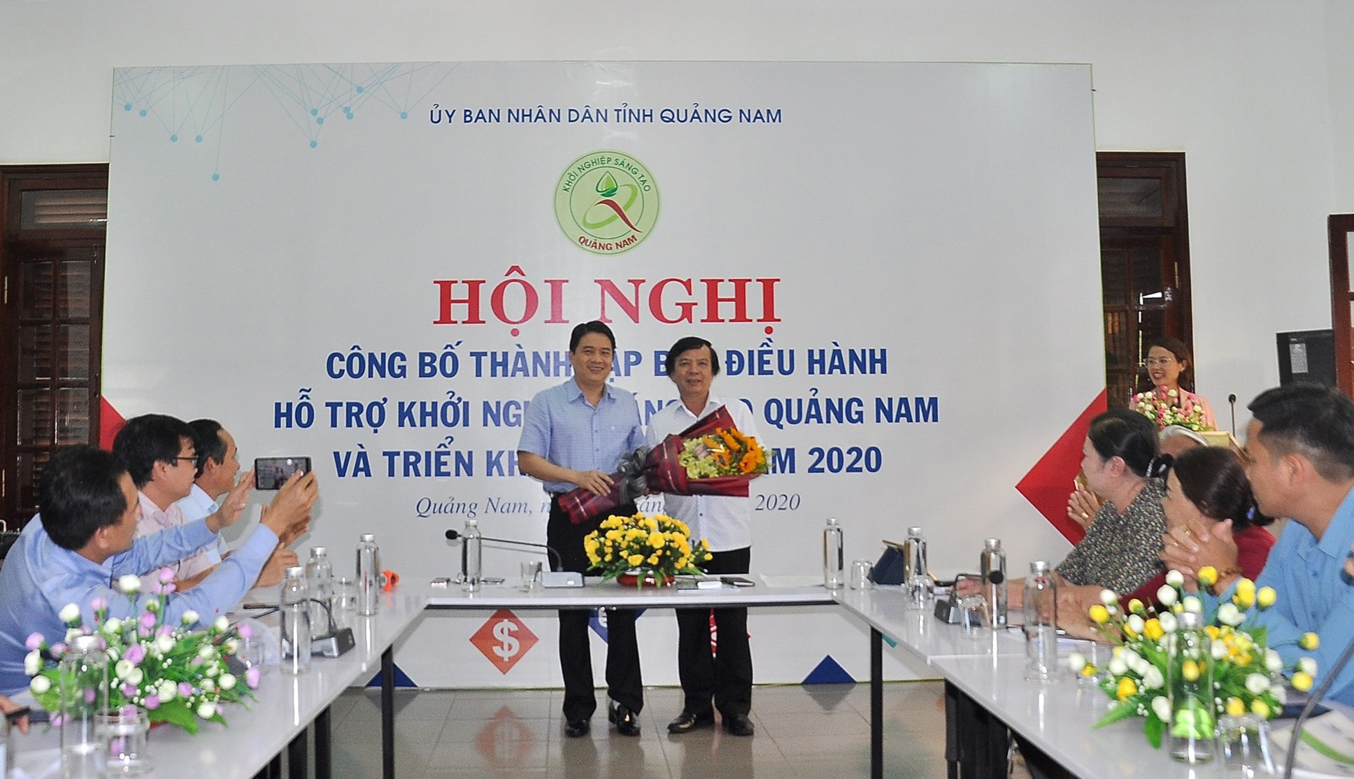 Ông Phạm Ngọc Sinh - Phó Giám đốc Sở KH-CN thay mặt Ban điều hành nhận hoa chúc mừng từ Phó Chủ tịch UBND tỉnh Trần Văn Tân. Ảnh: VINH ANH