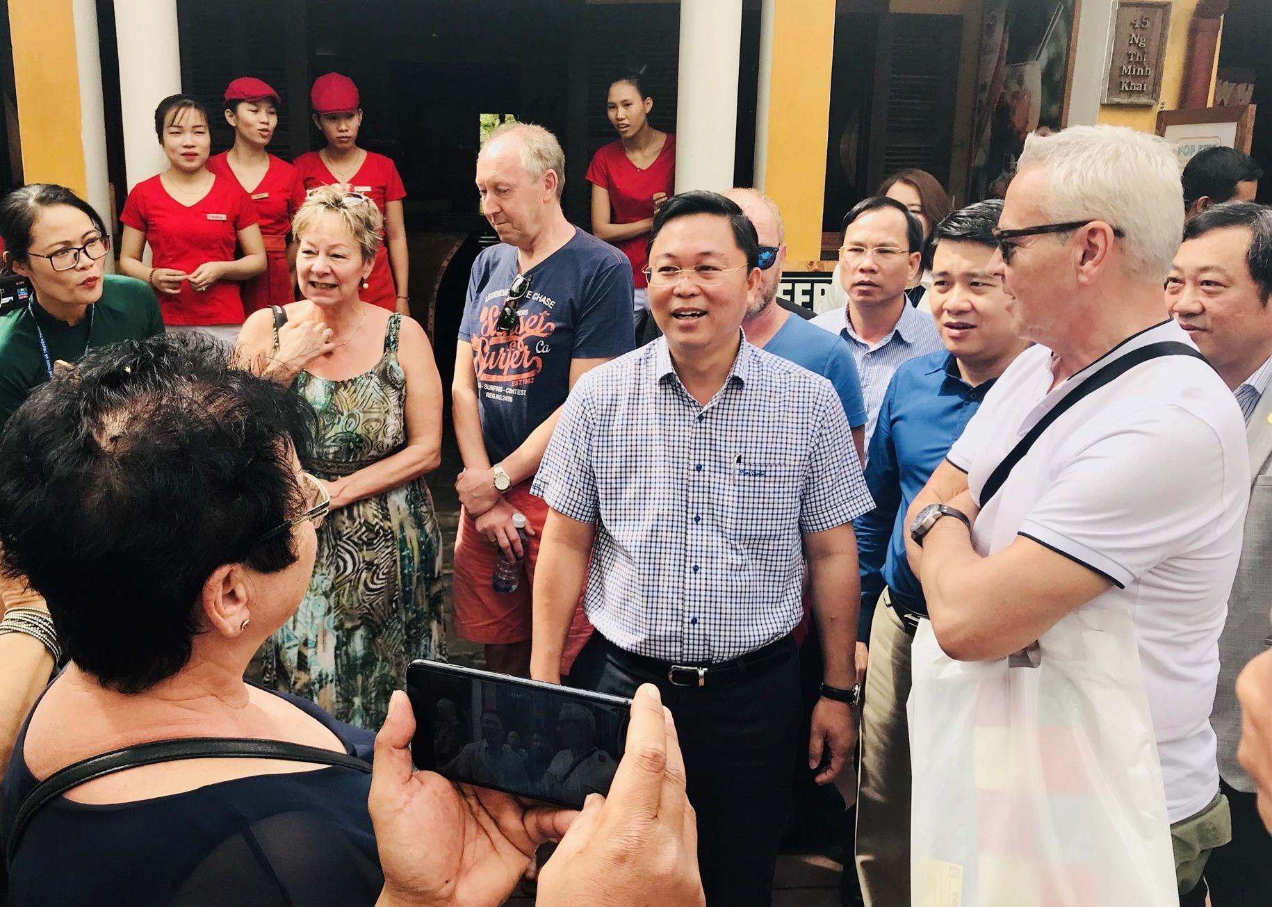 Chủ tịch UBND tỉnh Lê Trí Thanh trao đổi với du khách quốc tế trong khu vực phố cổ. Ảnh: T.V