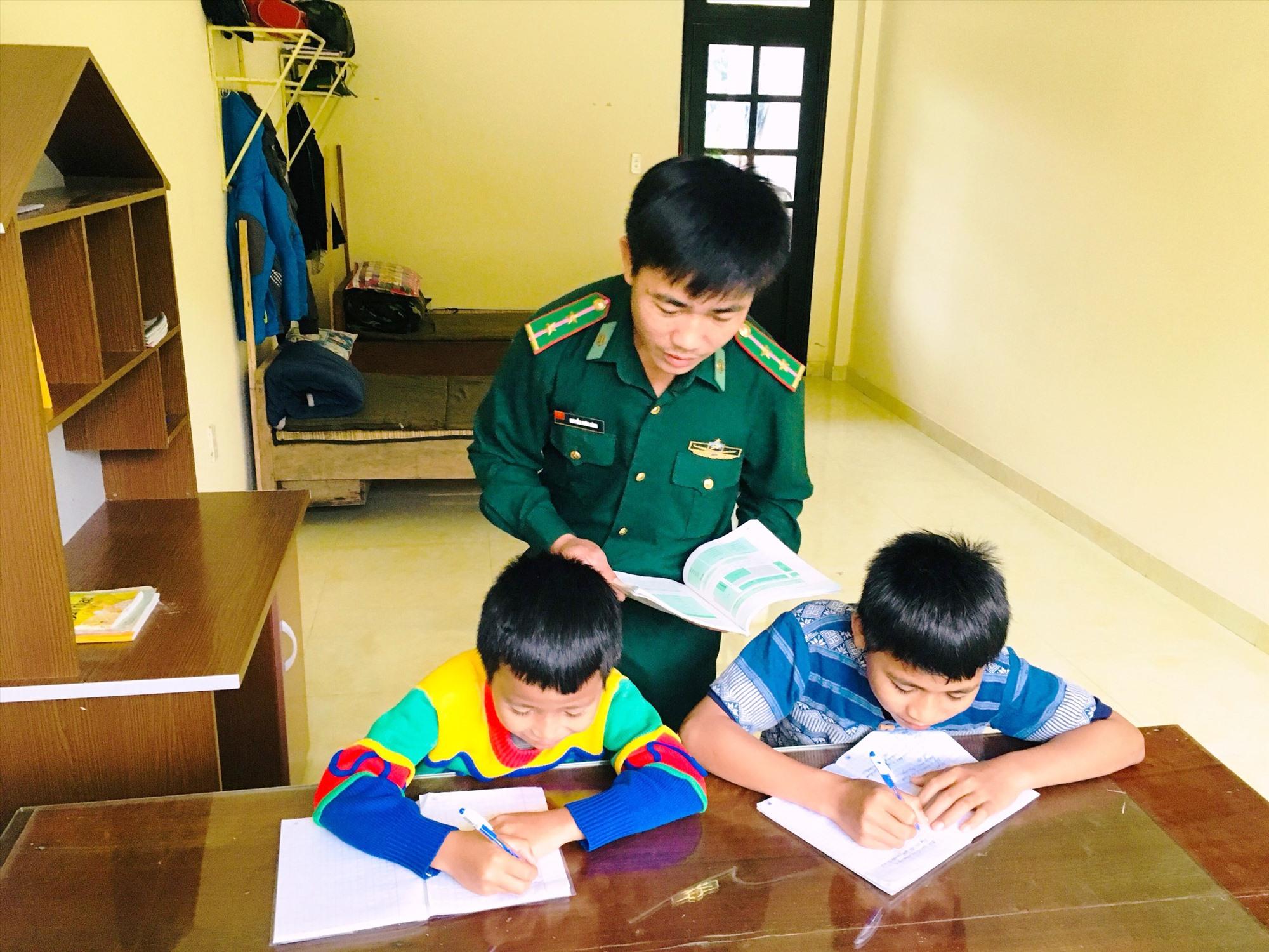 Chiến sĩ Đồn Biên phòng La Êê kèm cặp dạy hai em học bài. Ảnh: V.VINH