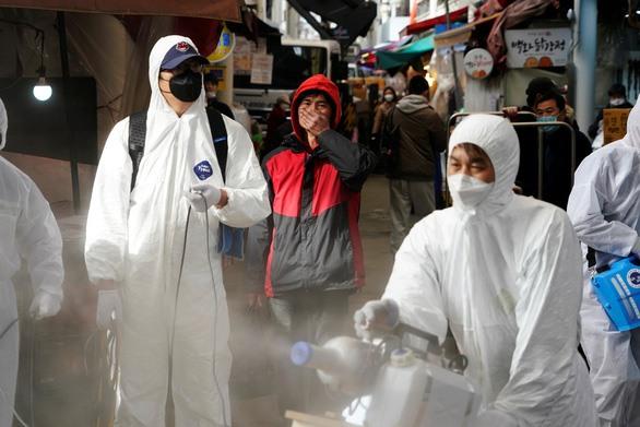 Nhân viên khử trùng một khu chợ truyền thống ở Seoul, Hàn Quốc, ngày 26-2 - Ảnh: REUTERS