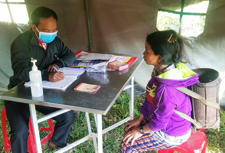 Bác sĩ Clâu Hín kiểm tra lịch trình của một phụ nữ Lào đến khám sức khỏe tại trạm kiểm soát. Ảnh: THÔNG NGUYỄN