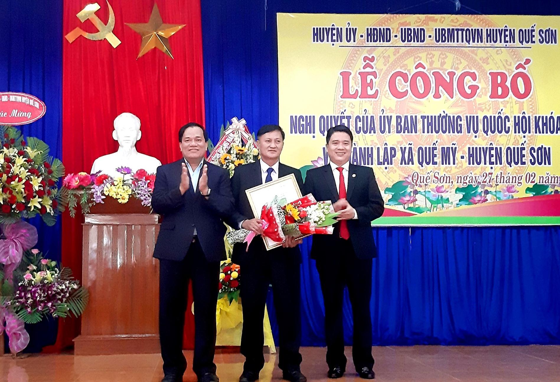 Phó Chủ tịch UBND tỉnh Trần Văn Tân cùng ông Lê Tấn Trung - Bí thư Huyện ủy Quế Sơn trao Nghị quyết thành lập xã Quế Mỹ và tặng hoa chúc mừng lãnh đạo địa phương. Ảnh: VĂN SỰ