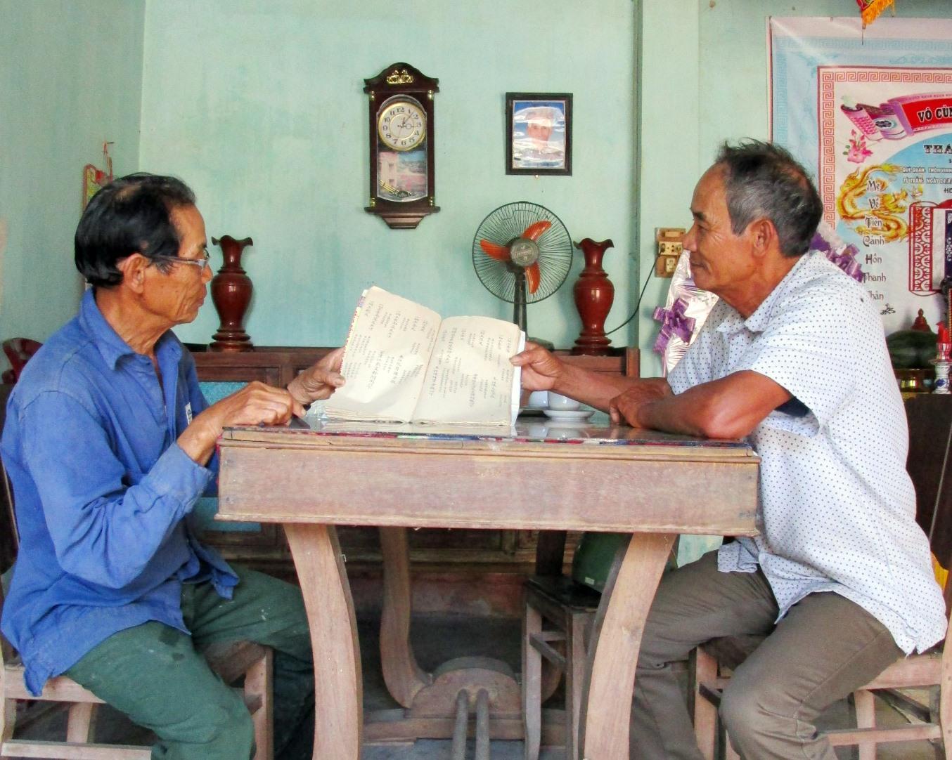 Các ông Nguyễn Văn Ngôn và Hồ Thắng Tùng bên cuốn điền bạ làng Địch Thái.