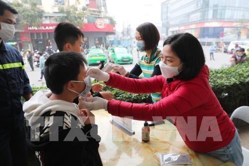 Hướng dẫn cách đeo khẩu trang y tế cho các em nhỏ. Ảnh: Thành Đạt - TTXVN
