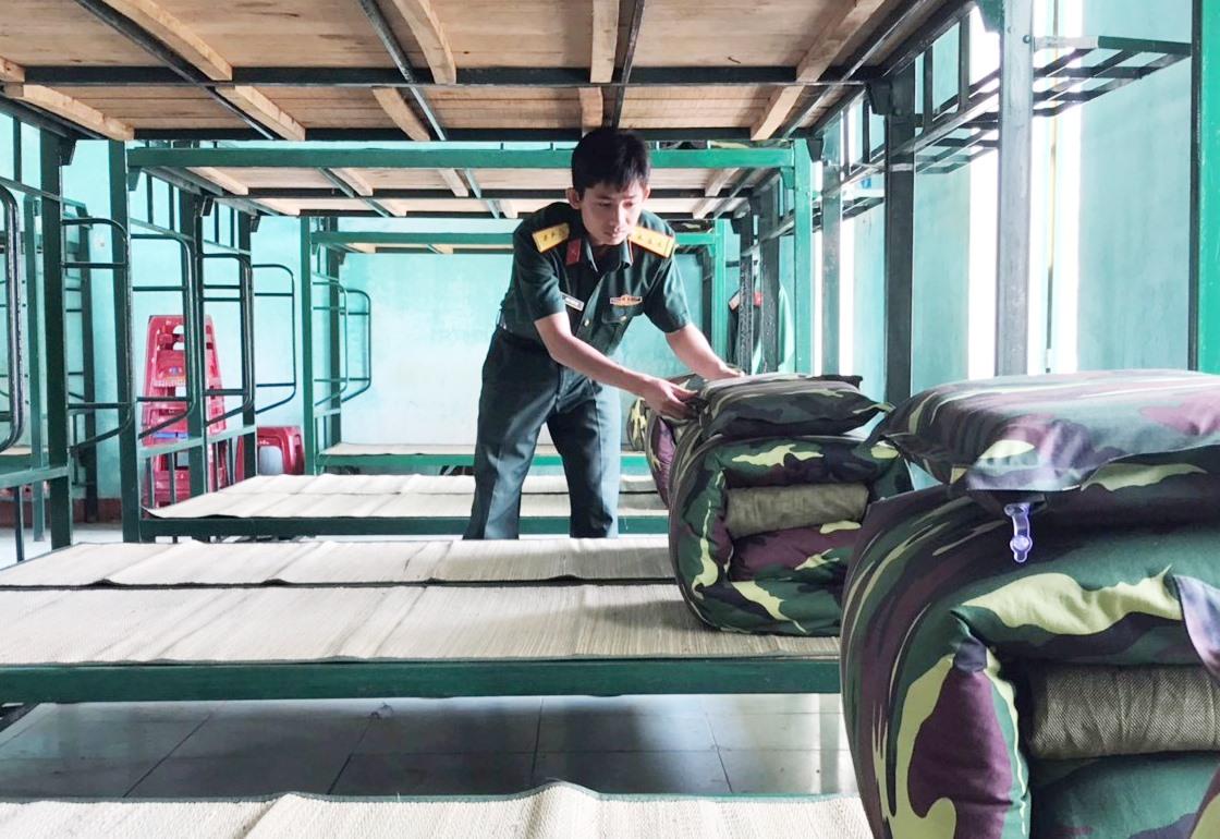 Thượng úy Châu Phước Hải - Đại đội trưởng Đại đội 2 Tiểu đoàn 1 kiểm tra từng giường nằm của chiến sĩ mới. Ảnh: NGỌC DIỆP