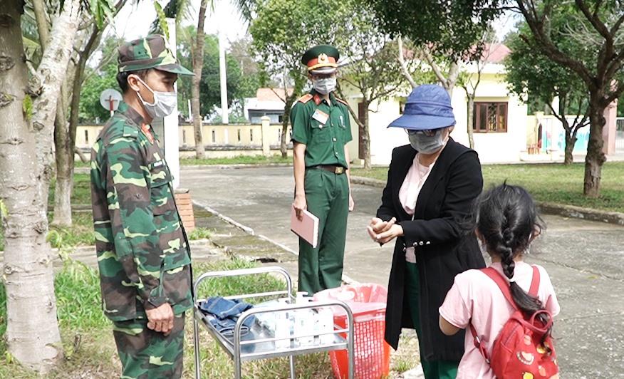 Công dân rửa tay và thay khẩu trang trước khi vào kiểm tra. Ảnh: PHAN VINH