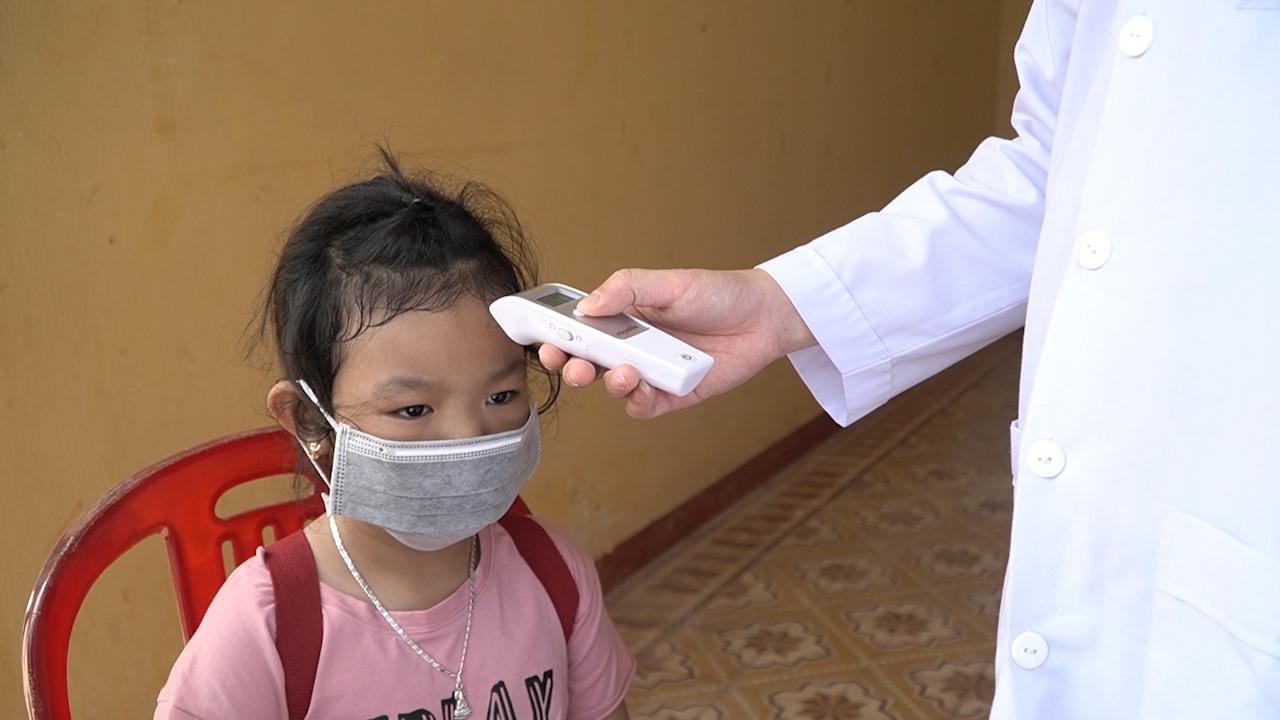 Công dân được đo thân nhiệt để kiểm tra sức khỏe. Ảnh: PHAN VINH
