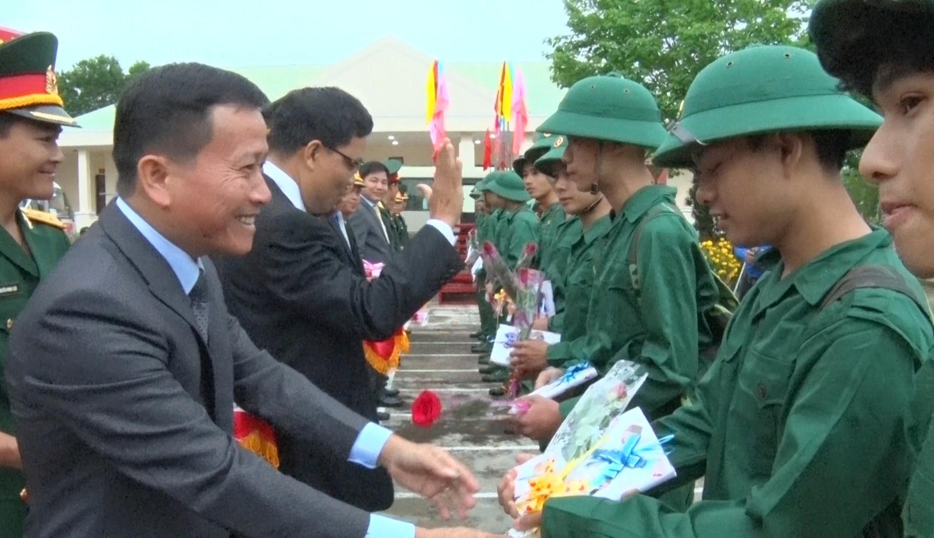 Đồng chí Thái Bình -Bí thư huyện ủy Nông Sơn tăng hoa và động viên thanh niên lên đường. Ảnh M.T