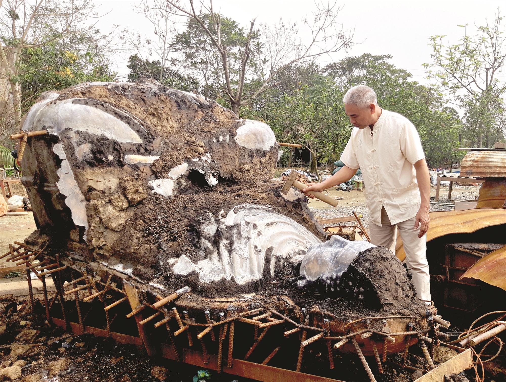Nghệ nhân Nguyễn Bá Châu với sản phẩm tượng đồng vừa tháo khuôn. Ảnh: PHAN HOÀNG