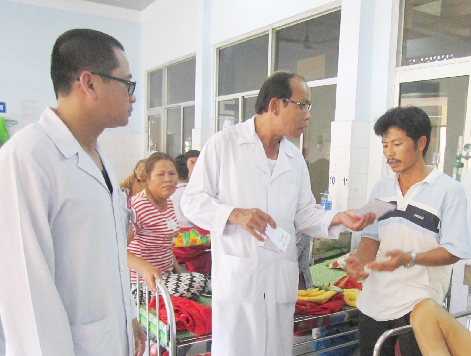 Bác sĩ Trần Phước Ta trao tiền hỗ trợ bệnh nhân nghèo. Ảnh: N.TRANG