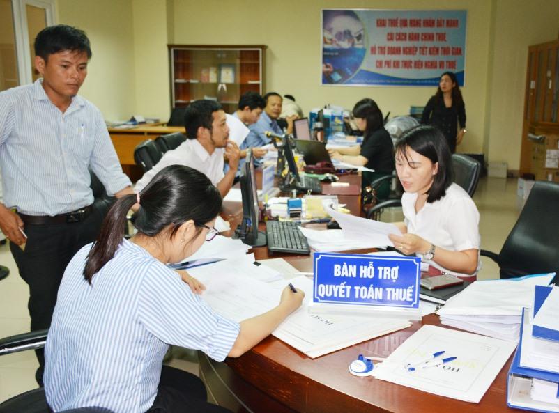 Cán bộ Cục Thuế Quảng Nam hỗ trợ về giải quyết thủ tục nộp thuế. Ảnh: V.DŨNG