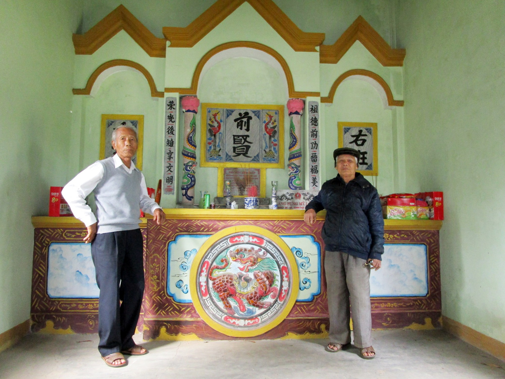 Các ông Huỳnh Văn Tường và Huỳnh Đức Huệ trước bàn thờ tiền hiền ở đình Sung Mỹ. Ảnh: PHÚ BÌNH