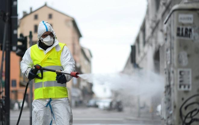 Nhân viên y tế phun thuốc khử trùng tại một quảng trường ở phía bắc Italy. Ảnh: Reuters